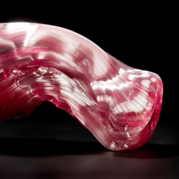 stretched and bent glass formation of abstract sculpture in pink