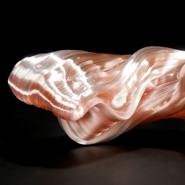 stretched and bent glass formation of abstract sculpture in pink and coral