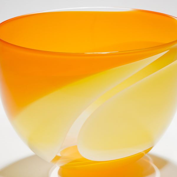 handblown glass sculpted bowl in orange with yellow waves