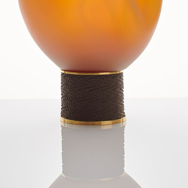 orange modern glass art sculpture of blob shape from blown glass resting on bronze base