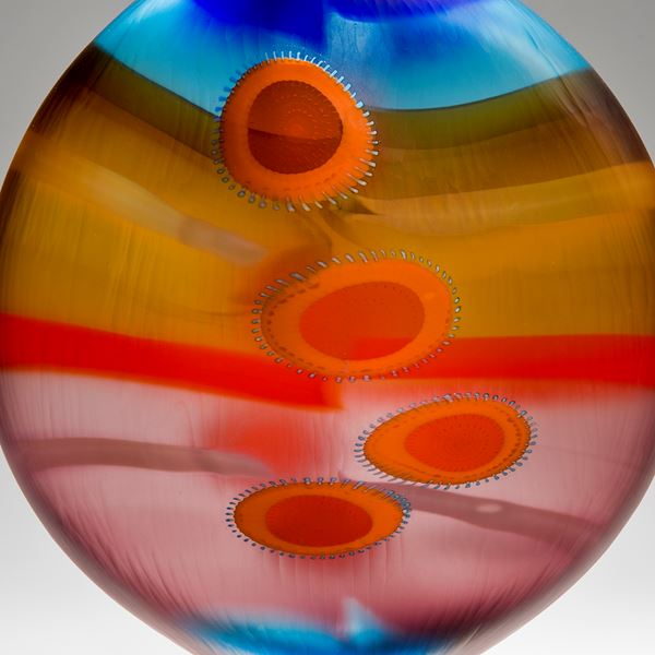 brightly coloured round glass vase with elliptical shapes