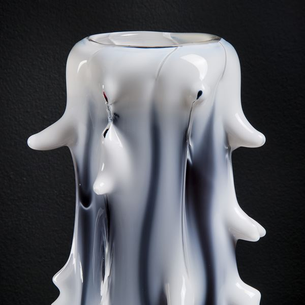tall white abstract glass sculptre with random protruding scale-like edges and black shading