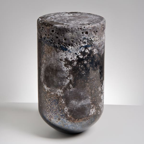 glass sculpture made to resemble natural stone with dark and light earthy tones in the shape of a bullet