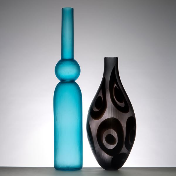 modern tall glass vessel sculpture with thin neck in dark grey and black circle patterns