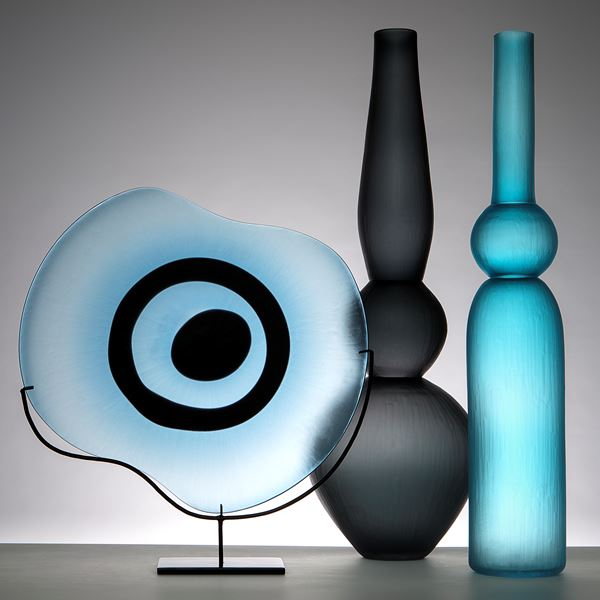 sculpted glass plate in light blue with black eye shape on metal stand
