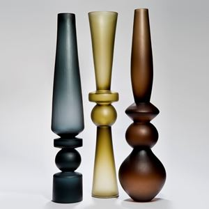 three tall art glass vases in dark blue, yellow and brown colours