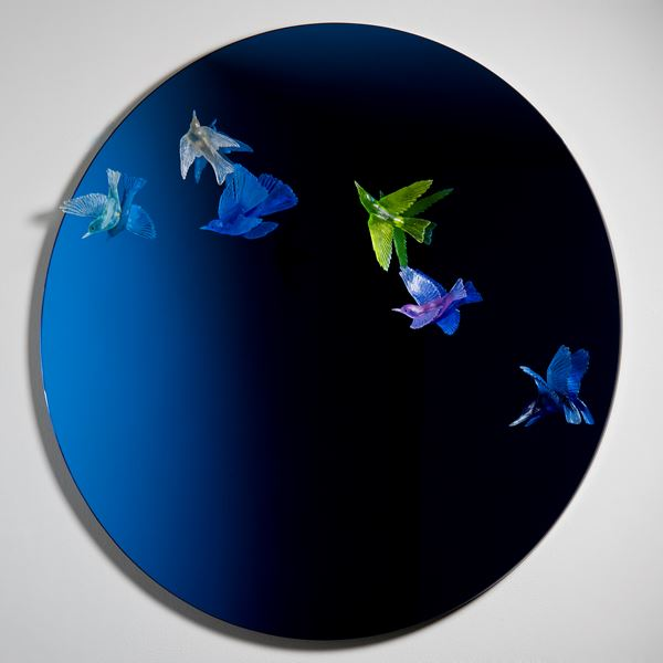 round blue art glass mirror with bird sculptures