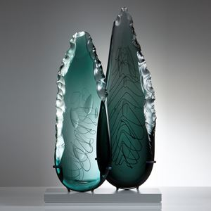 two leaf-shaped glass art sculptures in aqua and jade on clear rectangular base