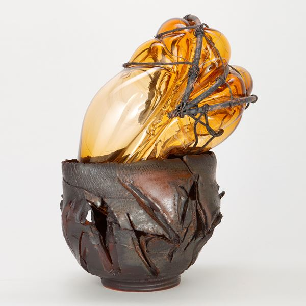 amber glass ornament in teracotta container with copper wire