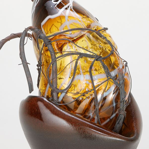 pear shaped amber glasswork art piece in basket with wire
