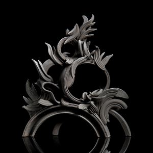 black stoneware sculpture in classical style with arcs and flares