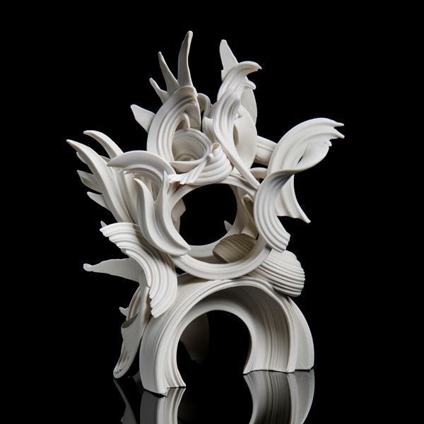white porcelain sculpture in classical style of arcs and flares intertwined