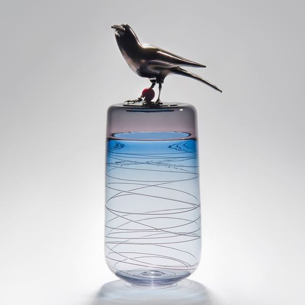 sculpted glass case in white, light blue and pink with helter skelter line pattern on exterior and stainless steel crow on top with red cherry