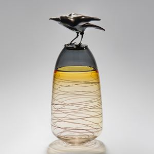 glass and steel sculpture of a crow atop a clear and yellow tinted vase with helter skelter pattern