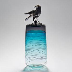sculpted glass vase in clear and turquoise with faint lines encircling exterior with stainless steel crow on top
