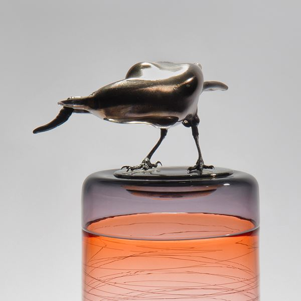 sculpted glass vase in clear and orange with faint lines encircling exterior with stainless steel crow on top
