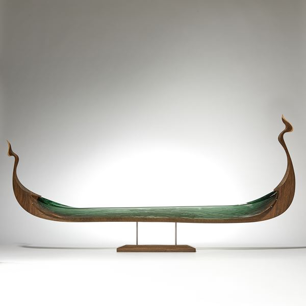 wood and glass sculpture of viking ship in green and brown on wooden base