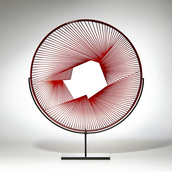 red and clear round sculptural glass plate made from handblown and cut glass with metal stand