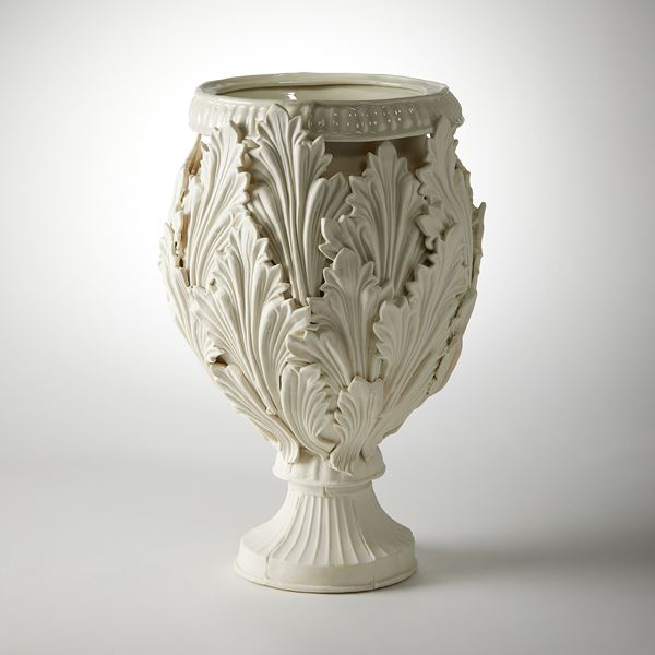 footed ornate vessel with leaf decoration handmade from porcelain
