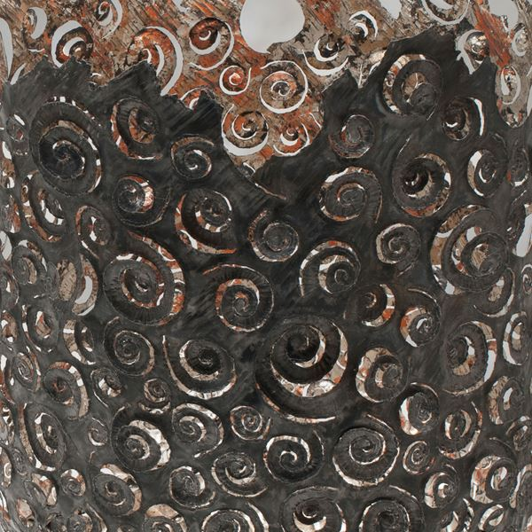dark brown and copper aged looking large metal vessel with hand cut organic ammonite swirling patter and irregular top edge