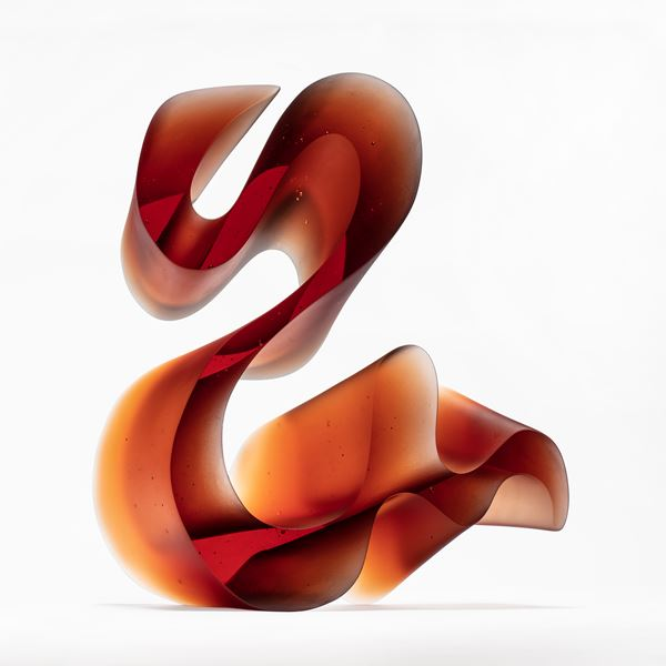amber red fluid lined sculpture with dramatic sweeping curves made from cast glass