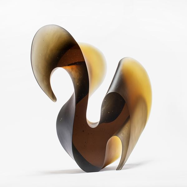 bronze brown fluid lined sculpture with dramatic sweeping curves made from cast glass