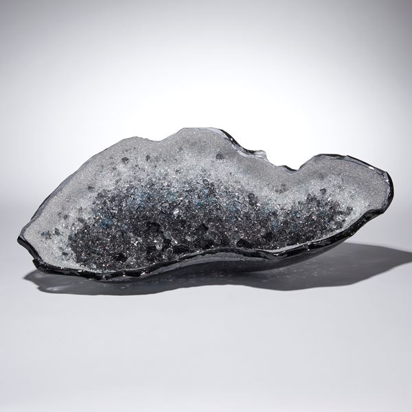 grey and blue oyster shell shaped glass sculpture with a twinkling crystal covered interior