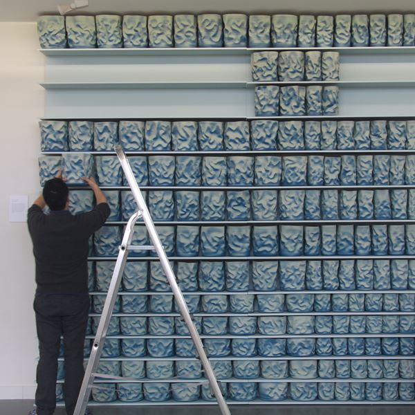 shelves of blue and cream scrunched and wrinkled looking hand thrown ceramic vessels creating a large wall mounted sculptural installation