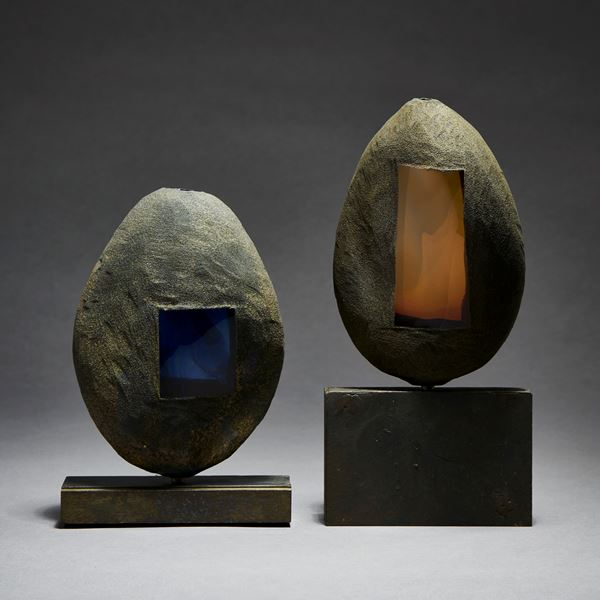 grey and brown hand made glass and metal ovoid shaped sculpture with square glass blue window and square geometric aged metal base