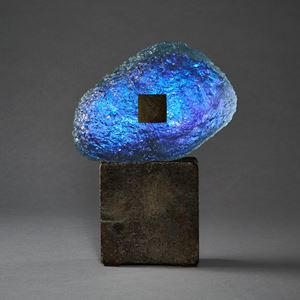 blue and dark brown meteoric hand formed glass amorphic sculpture on a weather cube base made steel