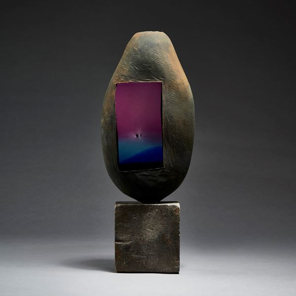 grey and brown rustic battered looking ovoid handmade glass sculpture with faded blue to purple glass window on a beaten metal cube base