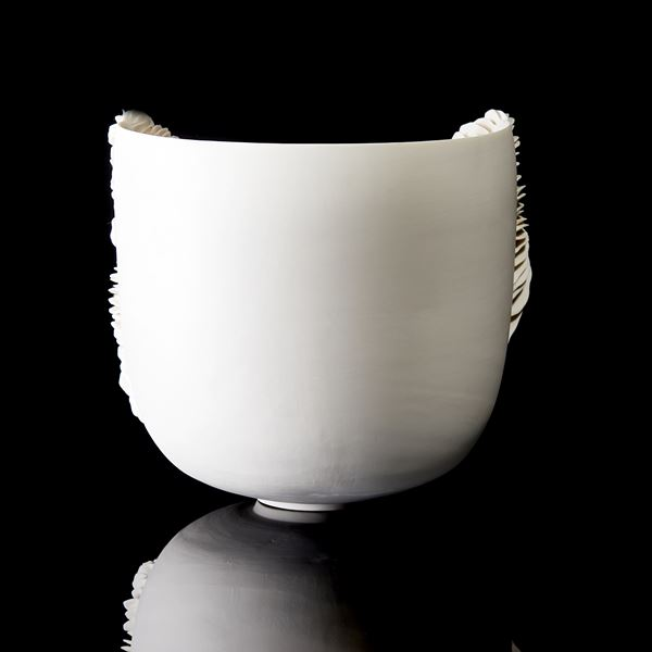 sculptural ceramic bowl with cut away side filled with ridged decoration handmade from porcelain
