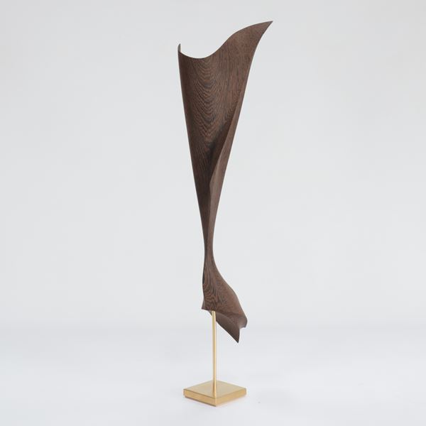 hanging cloth like form with gold detail and gold stand made from wood