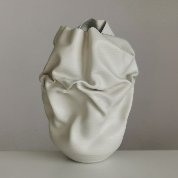 white crumpled and folded ceramic vessel with wobbly top edge handmade from clay