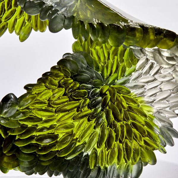 green and grey flowing squashed ring shaped textured sculpture made from cast glass