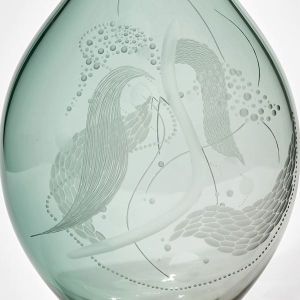 soft jade green see-through teardrop shaped handmade glass bottle with swirling cut surface patterns