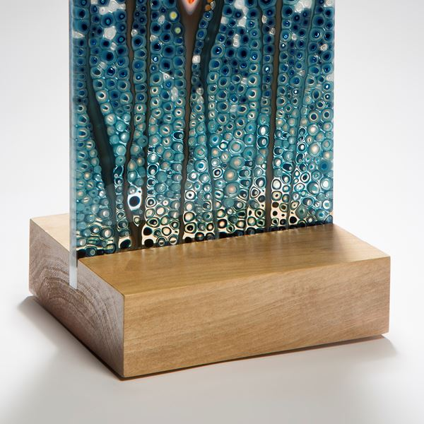 art glass sculptural panel in blue green and orange resting on wooden block