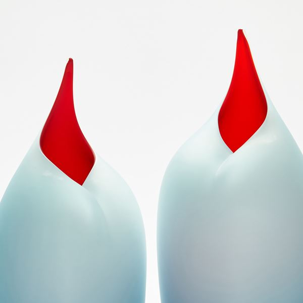 Stylised sleek tall bird shaped handmade paid of sculptures in blue and red