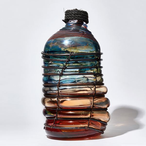 red blue and brown metal caged leaning bottle shaped glass sculpture with rope stopper detail