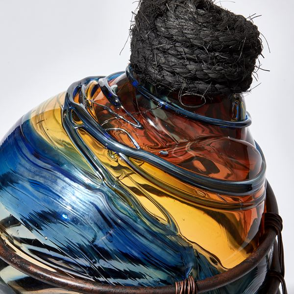 glass sculpture in the shape of an old bottle in blue clear and amber glass in a  copper cage with rope stopper