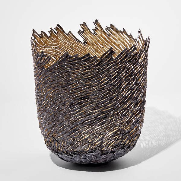 ornamental vessel in black and gold made from steel and precious metals