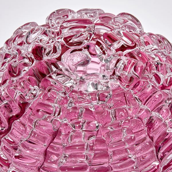 pink ridged globe shaped sculpture handmade and sculpted from glass with small top opening