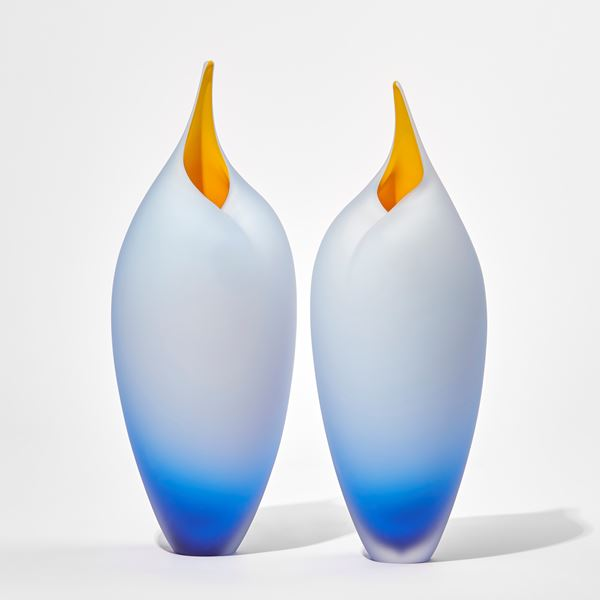 blue tall birds with rounded forms and open beaks and yellow mouths
