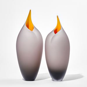 two bronze grey sleek tall rounded bird forms with pointed open beak with yellow interiors