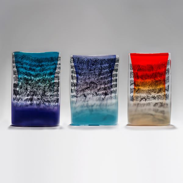 blue clear and purple tablet shaped handmade glass sculpture with black messy script