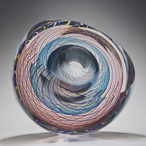art glass sculpture in donut shape with geometric patterns in pink light blue and clear glass