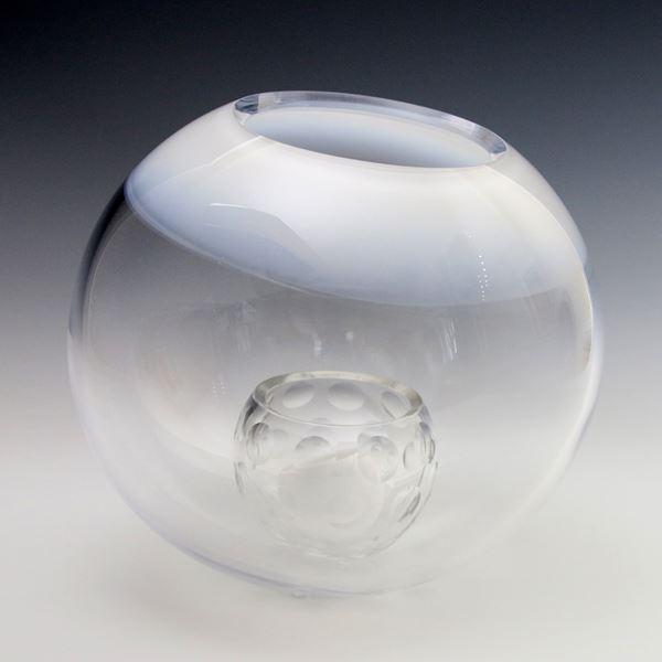 clear glass sculpture artwork of small round ball inside larger ball