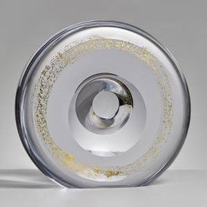 clear minimalist glass sculpture in the shape of a donut with spinkles of gold around the centre