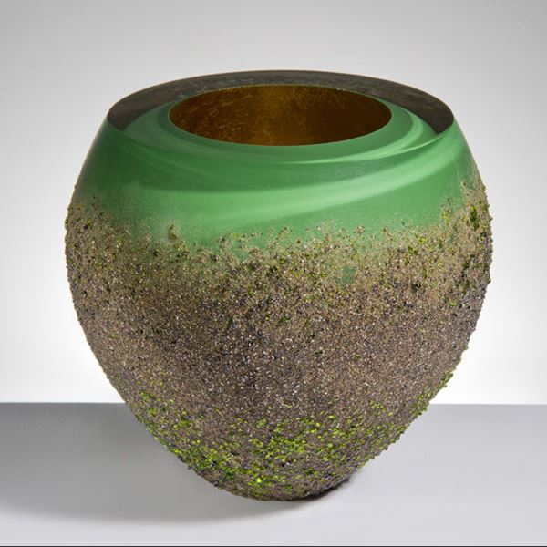 modern glass vase sculpture with open top in green swirls coated in earthy brown speckles from bottom to near top