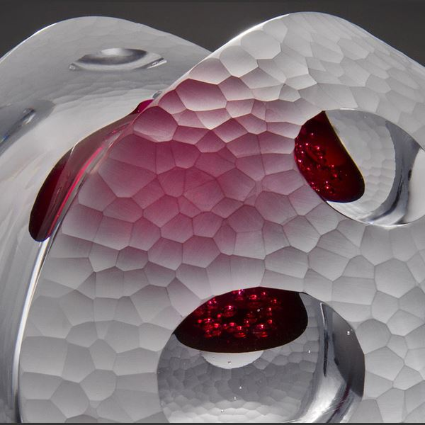 sculpted white glass artwork with pink tint